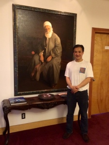 Michael Yen, Administrative Assistant to the Spiritual Assembly, stands next to a portrait of `Abdu'l-Bahá (son and successor of Bahá'u'lláh.