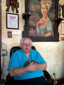Dr. John T. sits under the portrait of Marie Laveau