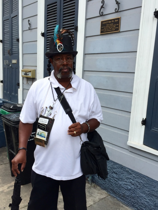 "NU'Awlons Natescott stands in front of where Marie Laveau's house once stood. The plaque reads, ""1020-22 Rue St. Ann - Marie Laveau and her children lived at this site between 1839 and 1895 before the circa 1905 construction of the existing cottage."